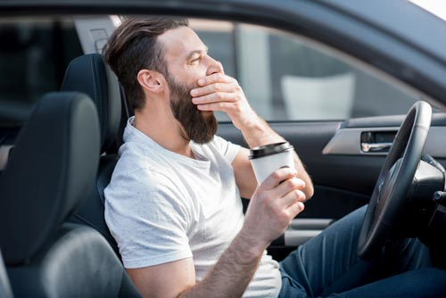 Man having trouble staying awake in car